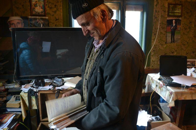 Vasiel Oanea răsfoiește unul dintre sutele de caiete cu poezii în fața unui mastodont tehnologic primit din Franța de la un nepot.